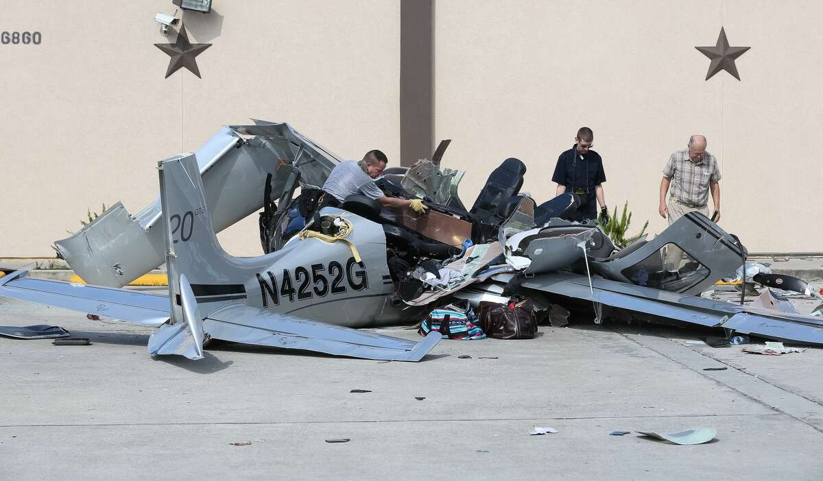 On Friday, June 10, 2016,a crew works to remove the wreckage of a small plane from a parking lot where it crashed Thursday killing three people, in Houston.