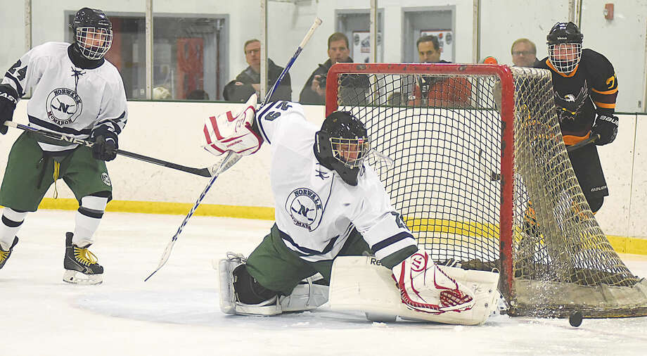 Hour photo/John Nash - Norwalk-McMahon goaltender Grant Riordon, center, gloves the puck away from the goal during a game earlier this season.
