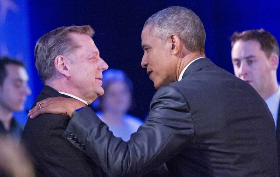 President Barack Obama, right, stops to greet Father Michael Pfleger, left, Pastor at Saint Sabina Catholic Church in Chicago during a commercial break at a CNN televised town hall meeting at George Mason University in Fairfax, Va., Thursday, Jan. 7, 2016. Obama's proposals to tighten gun controls rules may not accomplish his goal of keeping guns out of the hands of would-be criminals and those who aren't legally allowed to buy a weapon. In short, that's because the conditions he is changing by executive action are murkier than he made them out to be. (AP Photo/Pablo Martinez Monsivais)