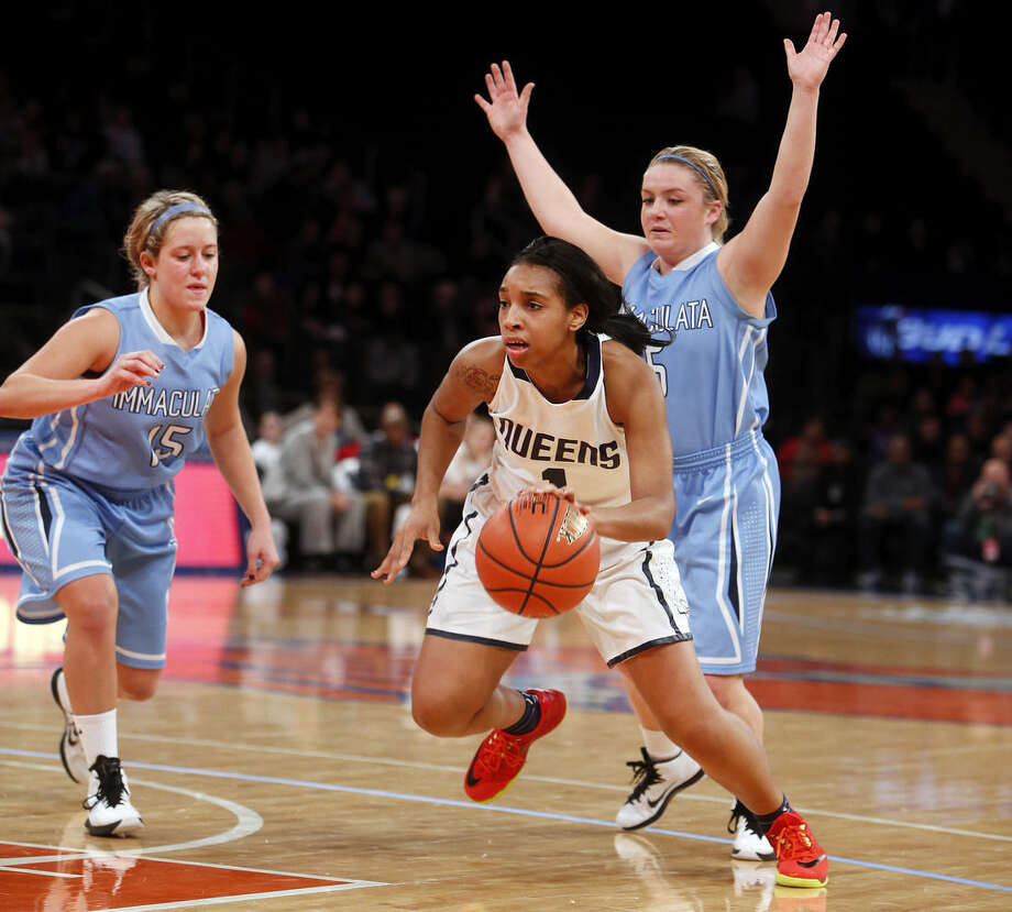 Queens' Imani Davidson (1) drives past Immaculata's Adriana Sciascia, left, and Mackie Fitzgerald (5) during the first half of an NCAA college basketball game Sunday, Jan. 4, 2015, in New York. (AP Photo/Jason DeCrow)
