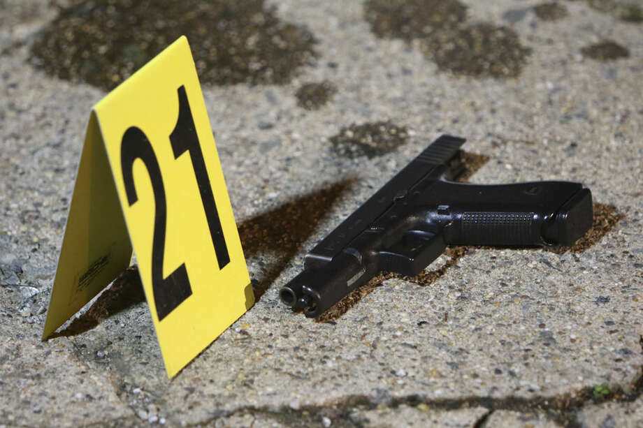 A gun sits by a marker following a shooting Friday, Jan. 8, 2016, in Philadelphia. A Philadelphia police officer was shot multiple times by a man who ambushed him as he sat in his marked police cruiser, authorities said. (AP Photo/Joseph Kaczmarek)