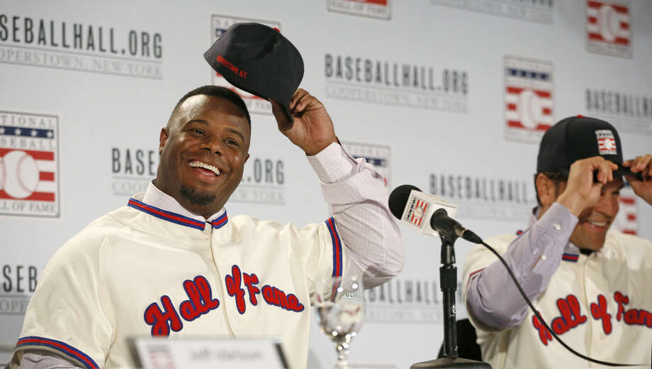 Ken Griffery Jr., left, reverses his cap after donning it backward at a news conference about his and Mike Piazza's election to baseball's Hall of Fame, Thursday, Jan. 7, 2016, in New York. Both men will be inducted into the Hall of Fame this summer. (AP Photo/Kathy Willens)