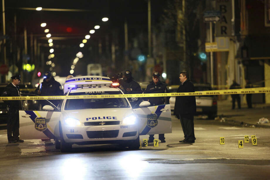 Officials investigate the scene of a shooting Friday, Jan. 8, 2016, in Philadelphia. A Philadelphia police officer was shot multiple times by a man who ambushed him as he sat in his marked police cruiser, authorities said. (AP Photo/Joseph Kaczmarek)