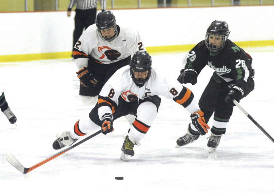 Hour photo/John NashStamford's Zach Rood (8) plays the puck before Norwalk-McMahon's Joe Laychak (26) can get to it as the Black Knights' Matt Tuccinardi looks on during Saturday's FCIAC hockey game in Stamford. The Black Knights won, 5-2.