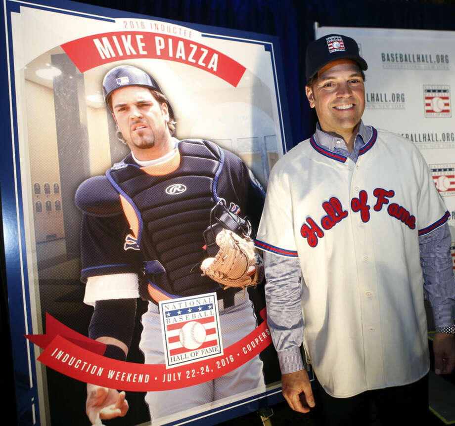 New York Mets catcher Mike Piazza poses with a photograph of himself at a press conference announcing that he and Ken Griffey Jr. were elected to baseball's Hall of Fame, Thursday, Jan. 7, 2016, in New York. Both men will be inducted into the Hall of Fame this summer. (AP Photo/Kathy Willens)