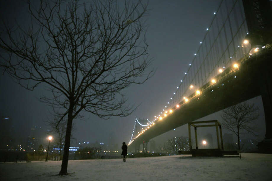 A woman walks through a park on the waterfront in Brooklyn near the Manhattan Bridge during a winter storm in New York, Thursday, Jan. 2, 2014. The storm is expected to bring snow, stiff winds and punishing cold into the Northeast. (AP Photo/Peter Morgan) / AP