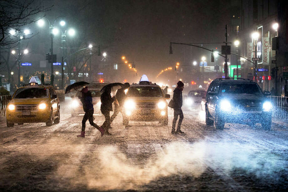 Pedestrians cross 34th Street and 6th Avenue under falling snow in Herald Square, Thursday, Jan. 2, 2014, in New York. The storm is expected to bring snow, stiff winds and punishing cold into the Northeast. (AP Photo/John Minchillo) / FR170537 AP