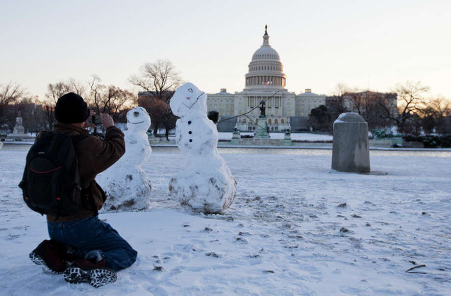 A man takes photos of snowmen with the Capitol in the background, Friday, Jan. 3, 2014, in Washington. After a storm blew through the Washington region overnight, roads are being cleared and many schools systems are closed. The federal government and the District of Columbia government will be open Friday, but workers have the option to take leave or telework. (AP Photo/ Evan Vucci) / AP