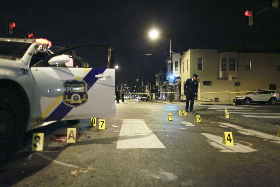 A law enforcement agent investigates the scene of a shooting Friday, Jan. 8, 2016, in Philadelphia. A Philadelphia police officer was shot multiple times by a man who ambushed him as he sat in his marked police cruiser, authorities said. (AP Photo/Joseph Kaczmarek)