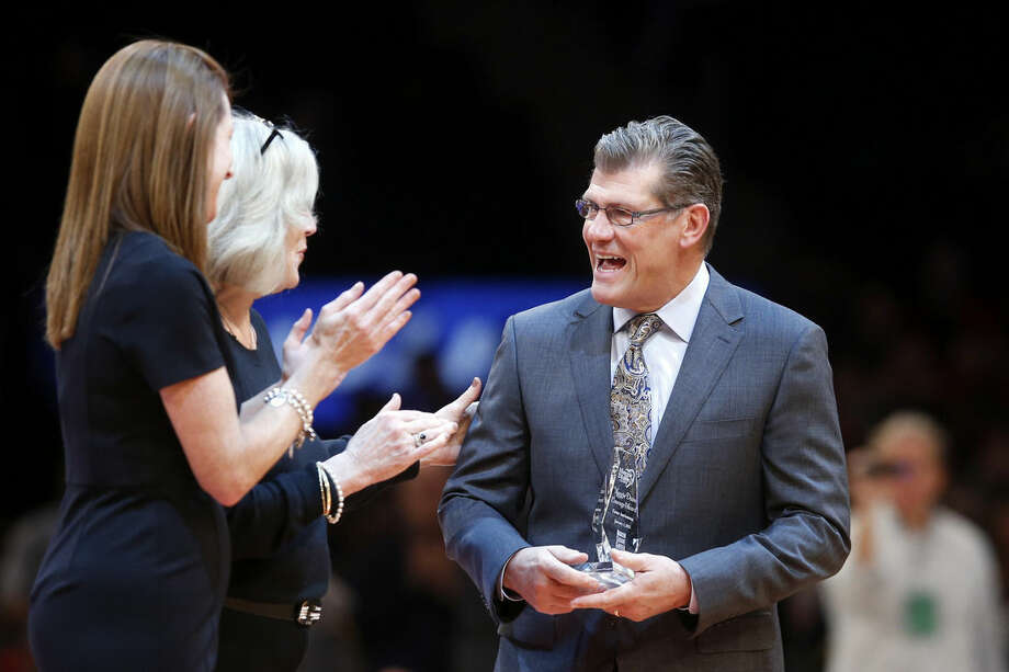 Connecticut coach Geno Auriemma is presented the Maggie Dixon Courage Award during a break in the second half action of an NCAA college basketball game between Immaculata and Queens, played before a matchup between Connecticut and St. John's, Sunday, Jan. 4, 2015, in New York. (AP Photo/Jason DeCrow)