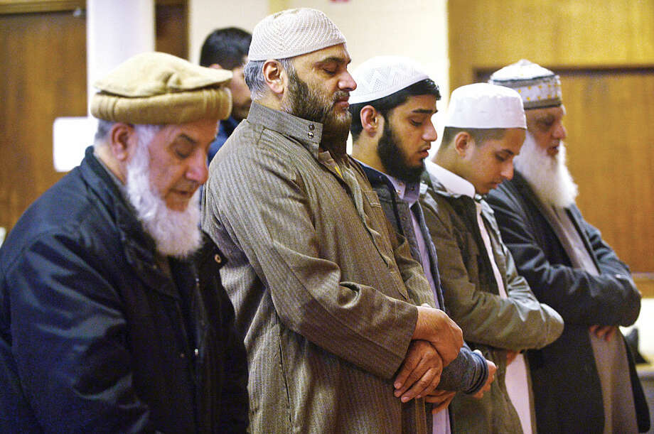 Hour photo / Erik Trautmann Muslims worship at the new home of the Al Madany mosque on Park St in Norwalk Friday.