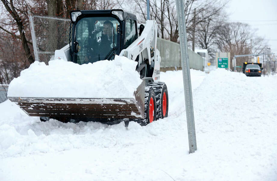 "Hour photo / Erik Trautmann Norwalk Department of Public Works clears sidewalk on East Ave after snowstorm Hercules dumped 6"" of snow on the area Friday."
