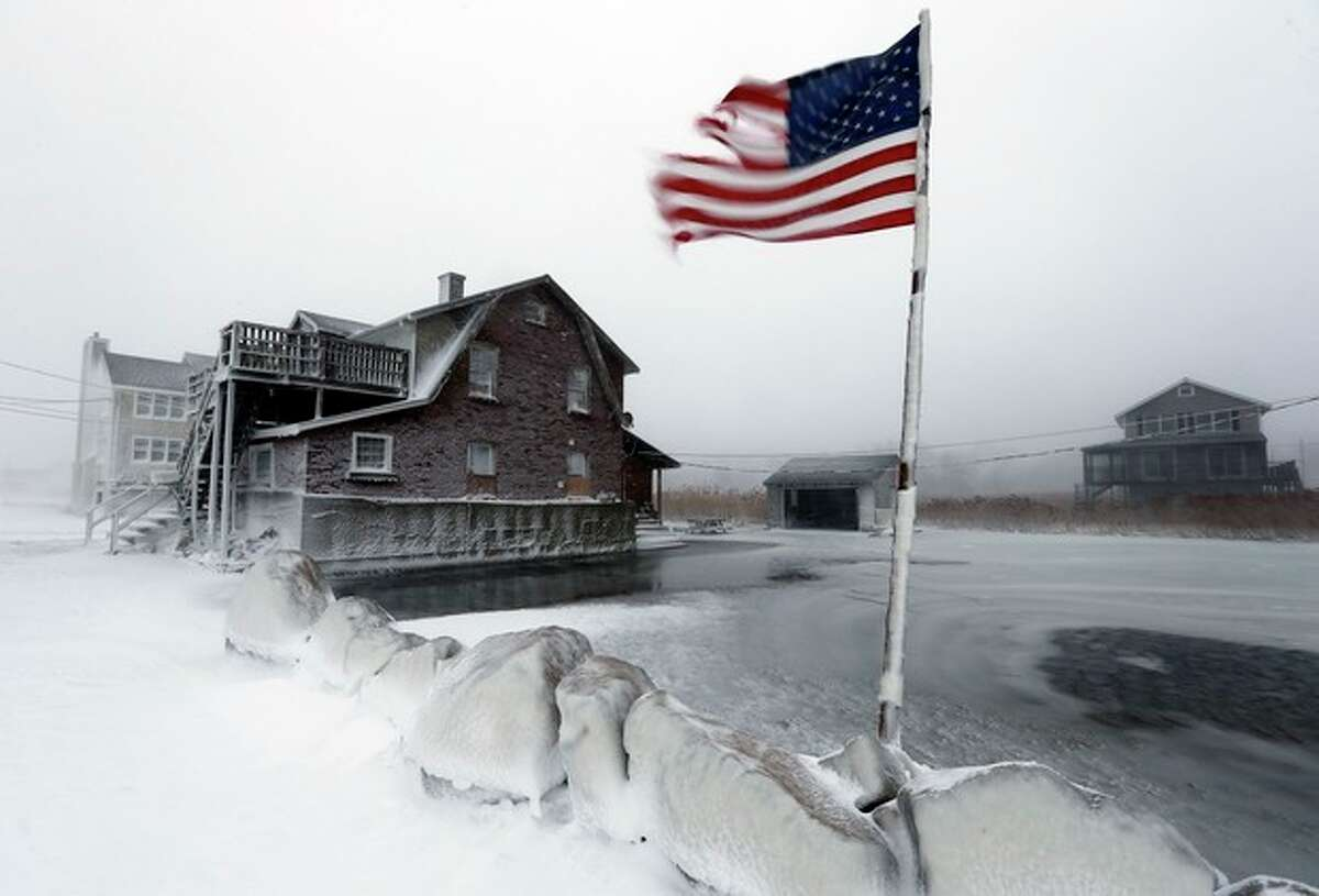 A tattered flag flies by a flooded yard along the shore in Scituate, Mass., Friday, Jan. 3, 2014. A blustering winter storm that dropped nearly 2 feet of snow just north of Boston, shut down major highways in New York and Pennsylvania and forced U.S. airlines to cancel thousands of flights nationwide menaced the Northeast on Friday with howling winds and frigid temperatures. (AP Photo/Michael Dwyer)