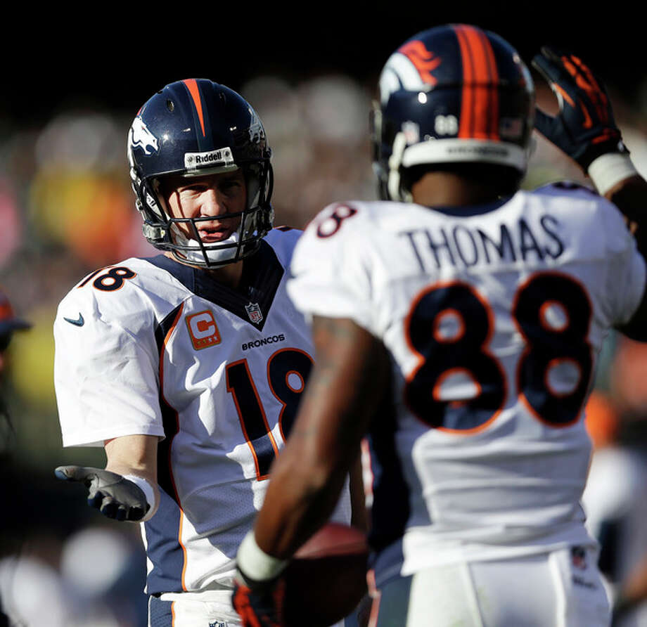 Denver Broncos quarterback Peyton Manning (18) celebrates with wide receiver Demaryius Thomas (88) after they connected for a 5-yard touchdown against the Oakland Raiders during the second quarter of an NFL football game, Sunday, Dec. 29, 2013, in Oakland, Calif. With that completion, Manning set the all-time single season passing yardage record. (AP Photo/Marcio Jose Sanchez) / AP