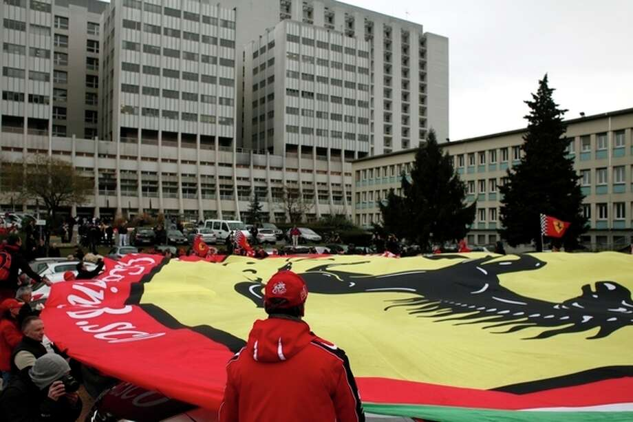 Michael Schumacher fans hold a giant banner to honor the Formula One Champion on his 45th birthday, Friday Jan. 3, 2014, in front of the Grenoble hospital where former seven-time Formula One champion Michael Schumacher is being treated after sustaining a head injury during a ski accident. Schumacher has been in a medically induced coma since Sunday, when he struck his head on a rock while on a family vacation. (AP Photo/Thibault Camus) / AP