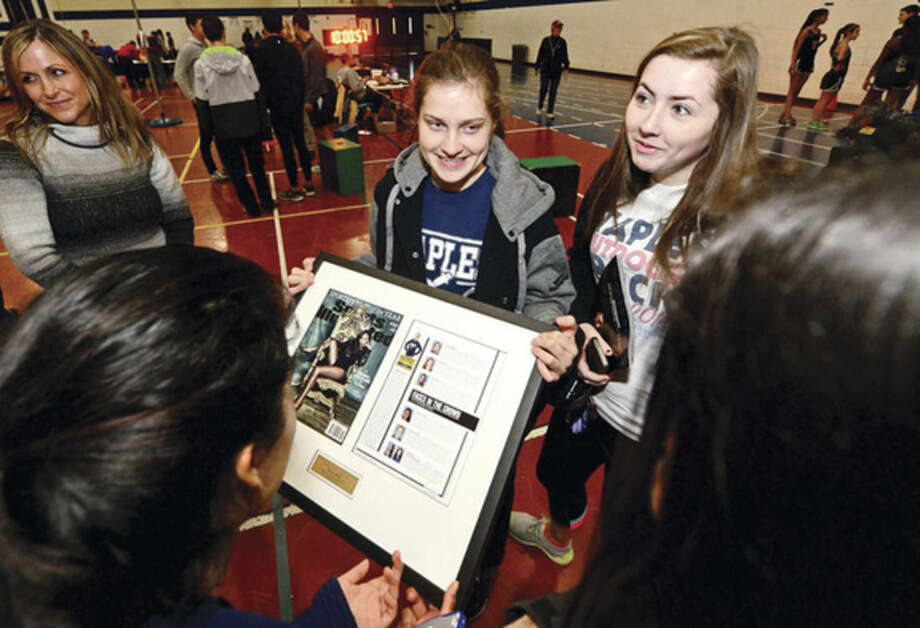 Hour photo / Erik TrautmannThree-time state and New England champ in cross country, Staples High School runner Hannah DeBalsi, shows off her award to friends including Erin Munley, after being honored as the Sports Illustrated High School Athlete of the Month for December on Saturday at the Staples track meet.