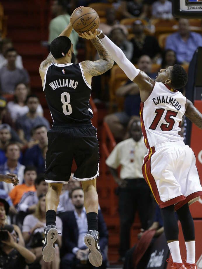 Brooklyn Nets guard Deron Williams (8) shoots over Miami Heat guard Mario Chalmers (15) during the first half of an NBA basketball game, Sunday, Jan. 4, 2015, in Miami. (AP Photo/Lynne Sladky)