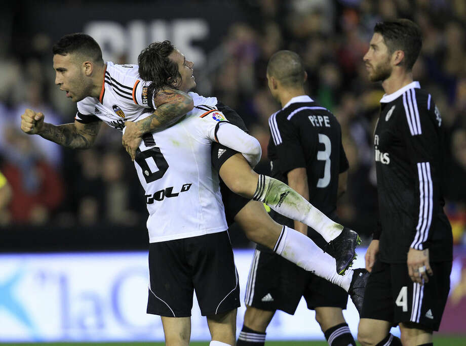 Valencia's Nicolas Otamendi, from Argentina, top center, celebrates his victory at the end a Spanish La Liga soccer match against Real Madrid at the Mestalla stadium in Valencia, Spain, on Sunday, Jan. 4, 2015. Valencia won the match 2 -1. (AP Photo/Alberto Saiz) is greeted by teammates