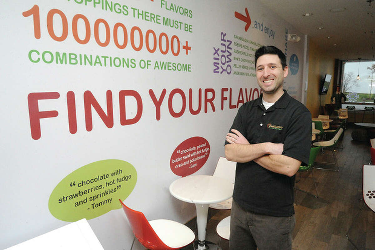 Photos by Matthew Vinci At left, Ryan Ventura, manager of Peachwave in Wilton Center, stands in the dining area of the Ridgefield Road yogurt shop, which offers 60 different flavors of the frozen dessert and an assortment of toppings.