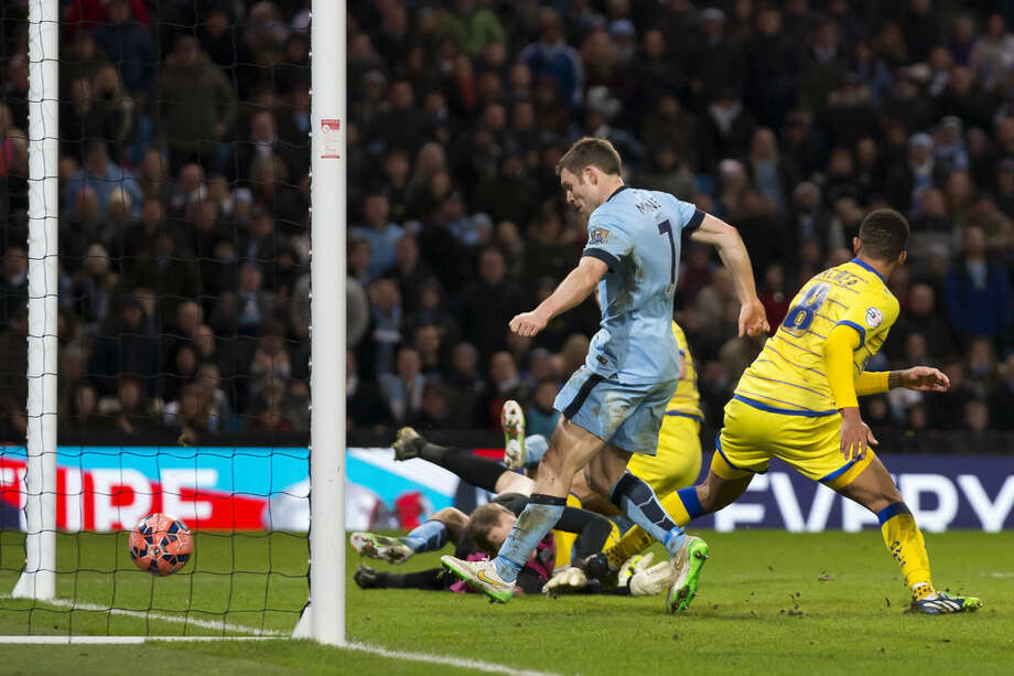 Manchester City's James Milner, centre, scores his second goal as his team beat Sheffield Wednesday 2-1 during their English FA Cup third round soccer match at the Etihad Stadium, Manchester, England, Sunday, Jan. 4, 2015. (AP Photo/Jon Super)