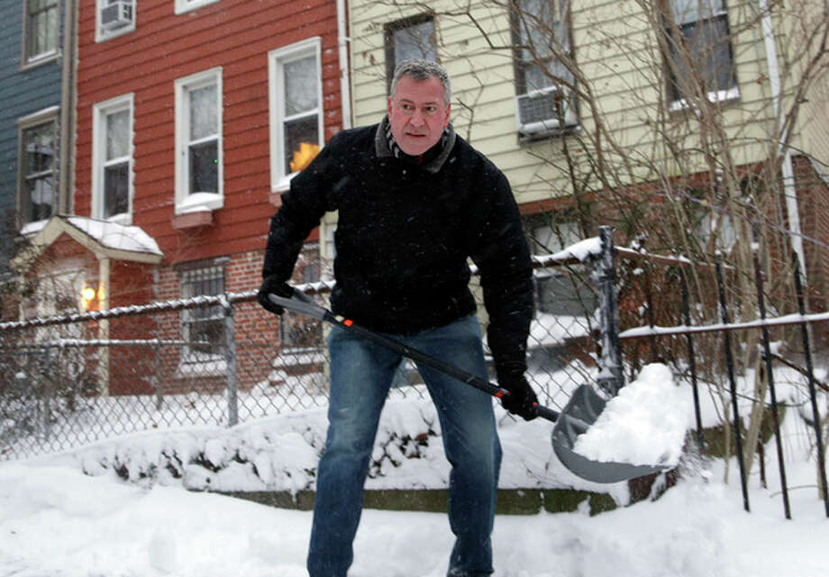 New York City Mayor Bill de Blasio shovels the sidewalk in front of his house in New York, Friday, Jan. 3, 2014. New York City public schools were closed Friday after up to 7 inches of snow fell by morning in the first snowstorm of the winter, and it the first test for the new mayor hours after he was sworn in. (AP Photo/Seth Wenig) / AP