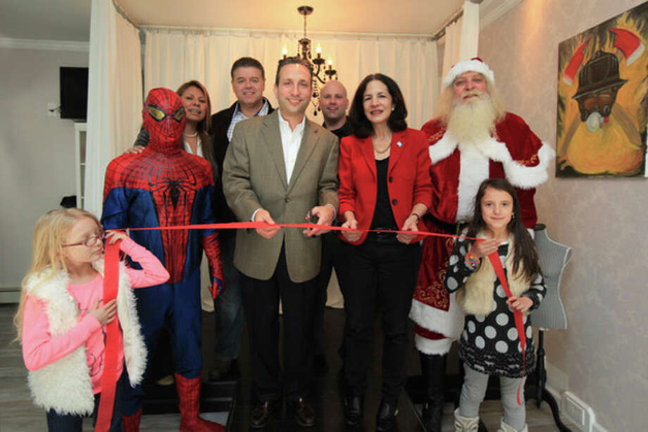 Hour photo / Chris PalermoState Sen. Bob Duff cuts the ribbon with Elena Abshire, Spiderman, owner Cecy Gillen, Artie Kassimas, owner Peter Gilen, state Rep. Gail Lavielle, Santa Claus (Rich Glica, and Emily Gillen at the grand opening of The Runway. / © 2013 Hour Newspapers All Rights Reserved.