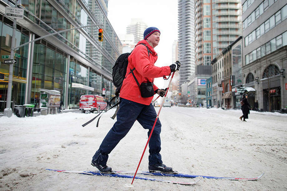 AP Photo / John MinchilloA pedestrian uses his cross-country skies on 58th Street during his morning commute, Friday, Jan. 3, 2014, in New York. New York City public schools were closed Friday after up to 7 inches of snow fell by morning in the first snowstorm of the winter. / FR170537 AP