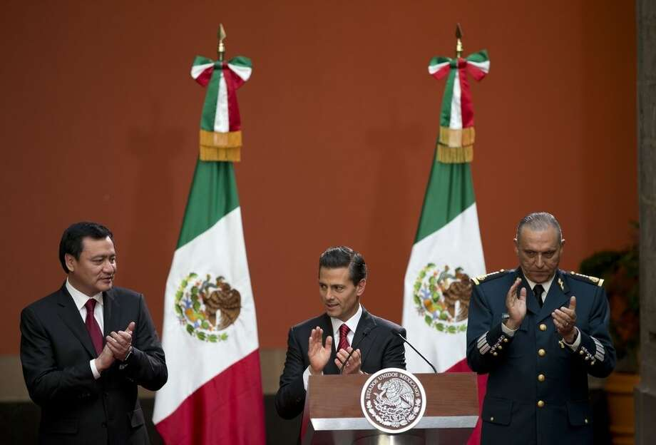 "Mexican President Enrique Pena Nieto, flanked by Interior Minister Miguel Angel Osorio Chong, left, and National Defense Secretary Slavador Cienfuegos Zepeda, applauds during a press conference following the capture of fugitive drug lord Joaquin ""El Chapo"" Guzman, in Mexico City, Friday, Jan. 8, 2016. Pena announced that Guzman had been recaptured six months after escaping from a maximum security prison. (AP Photo/Rebecca Blackwell)"