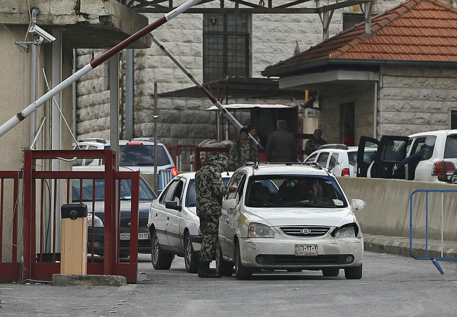 A soldier checks the passports of Syrian citizens at the gate at the Lebanese border crossing point of Masnaa, eastern Bekaa Valley, Lebanon, Monday, Jan. 5, 2015. Lebanon began imposing unprecedented restrictions Monday on the entry of Syrians, as the tiny country with a fragile sectarian balance struggles to cope with well over a million refugees fleeing the civil war next door. (AP Photo/Hussein Malla)