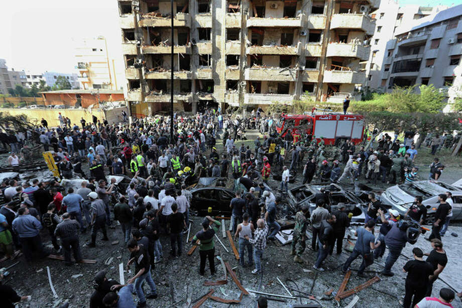 FILE - In this file photo taken Tuesday, Nov. 19, 2013, Lebanese people gather at the scene where two explosions have struck near the Iranian Embassy in Beirut, Lebanon. DNA tests confirmed that a man in Lebanese custody is the suspected leader of an al-Qaida-linked group that has claimed responsibility for bombings across the Middle East, the Lebanese army said Friday, Jan. 3, 2014. The latest attack claimed by the group, the Abdullah Azzam Brigades, was the Nov. 19 double bombing of the Iranian Embassy in Beirut that killed at least 23 people and wounded dozens. (AP Photo/Bilal Hussein, File) / AP