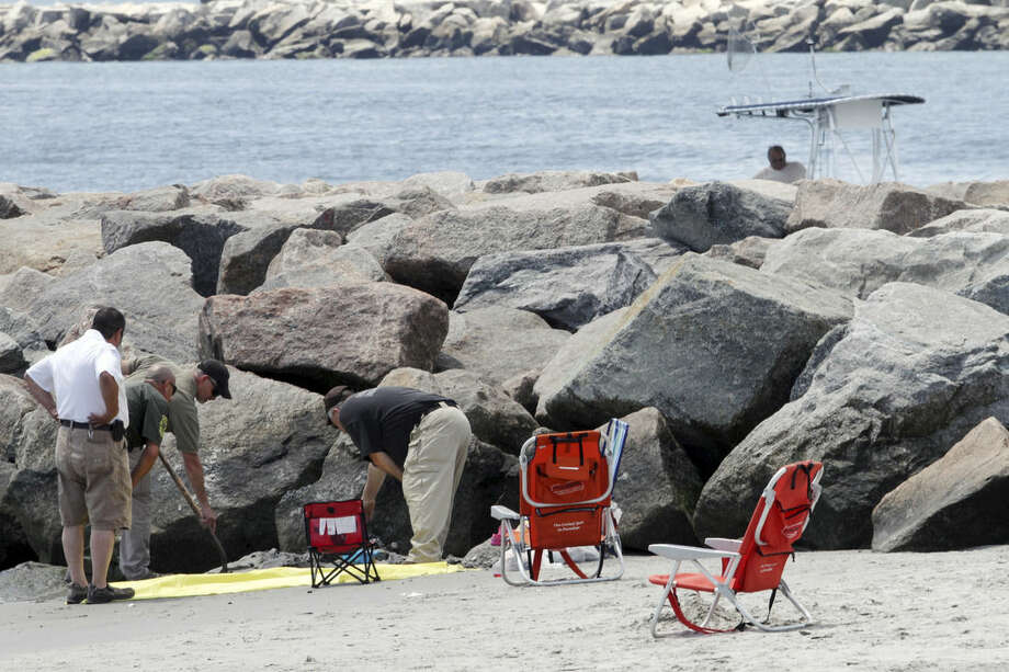 FILE- In this July 11, 2015 file photo, authorities investigate a blast that threw a beachgoer into a nearby jetty at Salty Brine beach in Narragansett, R.I. Scientists determined that the explosion was probably caused by the combustion of hydrogen that had built up around the cable. The U.S. Coast Guard said there are 47 sites in 12 states where there may be an inactive cable similar to the one that caused the explosion in Rhode Island. Michigan, with 21 potential sites, has the most, according to information released to The Associated Press through an open records request. (Steve Szydlowski/Providence Journal via AP, File)