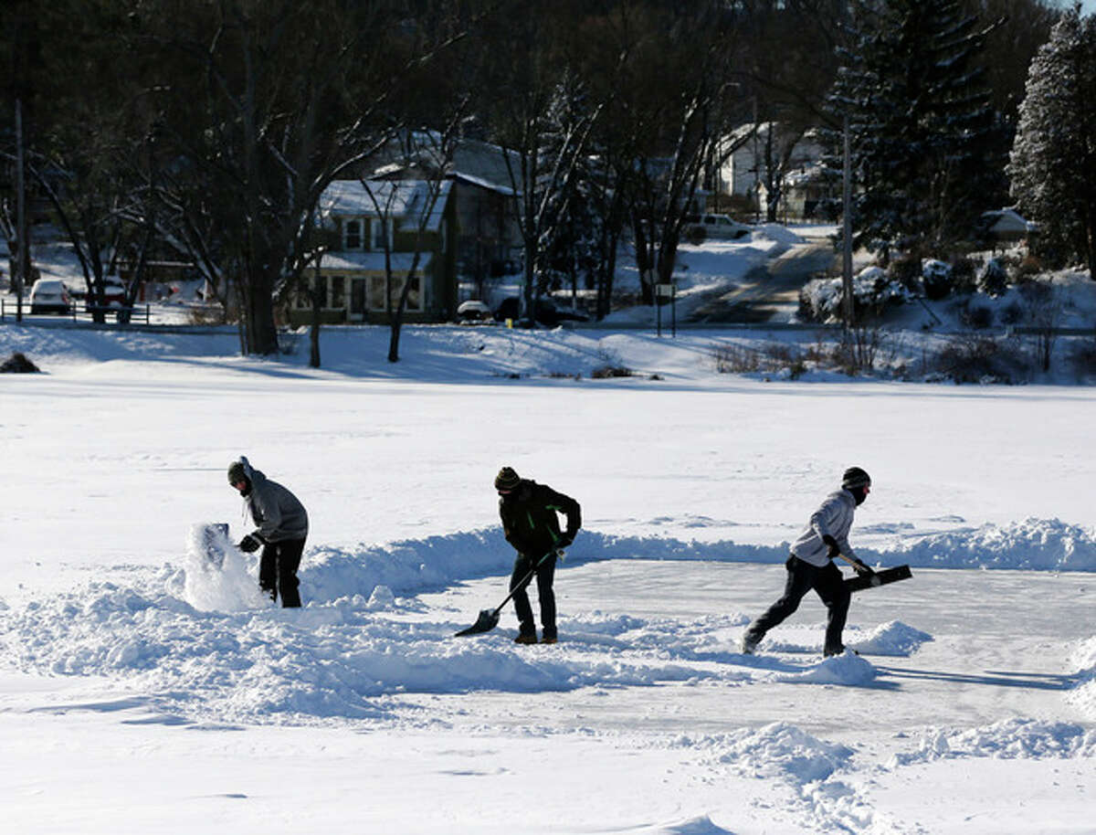 Alex Herrick, Adam Scirico and Peter Herrick clear a section of Hampton Manor Lake to play ice hockey on Friday, Jan. 3, 2014, in East Greenbush, N.Y. Upstate New York on Friday had temperatures in the single digits with below-zero wind chills. (AP Photo/Mike Groll)