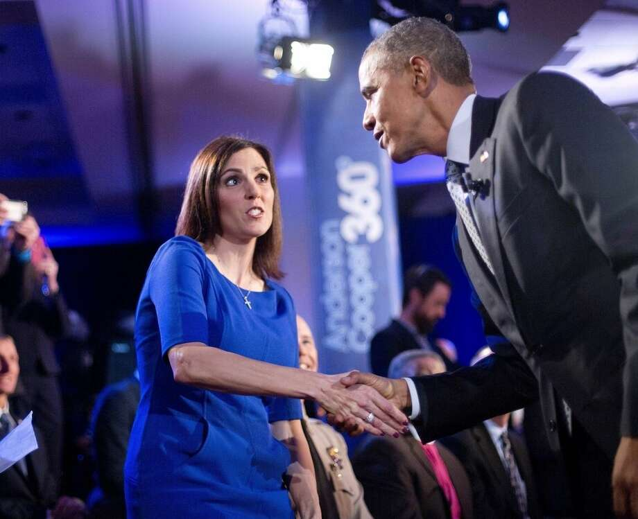 President Barack Obama, right, walks over to greet Taya Kyle, left, widow of U.S. Navy SEAL Chris Kyle, during a commercial break at a CNN televised town hall meeting at George Mason University in Fairfax, Va., Thursday, Jan. 7, 2016. Obama's proposals to tighten gun controls rules may not accomplish his goal of keeping guns out of the hands of would-be criminals and those who aren't legally allowed to buy a weapon. In short, that's because the conditions he is changing by executive action are murkier than he made them out to be. (AP Photo/Pablo Martinez Monsivais)
