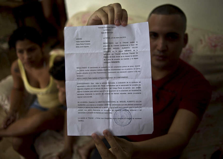 FILE - In this Jan. 9, 2015 file photo, dissident Miguel Alberto Ulloa, 25, poses for a photo in his home, holding his release document, a day after his release from jail in Havana, Cuba. About 20 of 53 freed dissidents have decided not to leave Cuba, some because they've abandoned political activism. But others want to stay and work to change the government. (AP Photo/Ramon Espinosa, File)