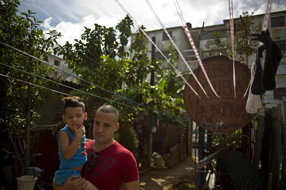 FILE - In this Jan. 9, 2015 file photo, a day after his release, dissident Miguel Alberto Ulloa, 25, holds his son next to a water tank painted with the acronym for the United States and his country's name, outside his home in Havana, Cuba. President Barack Obama says he'll travel to Cuba in 2016 if his presence will improve human rights on the island. The fate of 53 political prisoners freed a year ago under his detente push shows how difficult that may be. At least 35 have left or are seeking to leave, reducing the ranks of a weak opposition movement. Among the rest, at least six are back in prison, and others have abandoned activism. (AP Photo/Ramon Espinosa, File)
