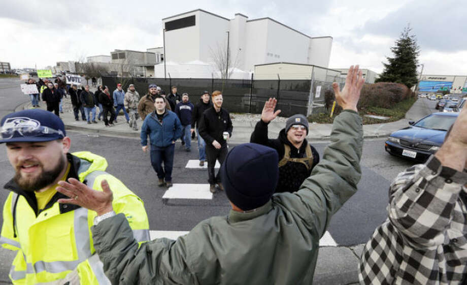 FILE - In this Dec. 18, 2013, file photo shows a small group of machinists union members are greeted by a supporter as they march away from a Boeing factory building toward the machinists' union hall in Everett, Wash. Boeing's contract proposal to machinists in the Puget Sound region would likely increase some workers' annual base salaries to more than $100,000 in the coming years. The contract offer going to a vote this week would slow the growth of machinists' wages starting in 2016, but workers would still get regular cost-of-living adjustments and an extra 1 percent pay increase every other year. (AP Photo/Elaine Thompson, File)