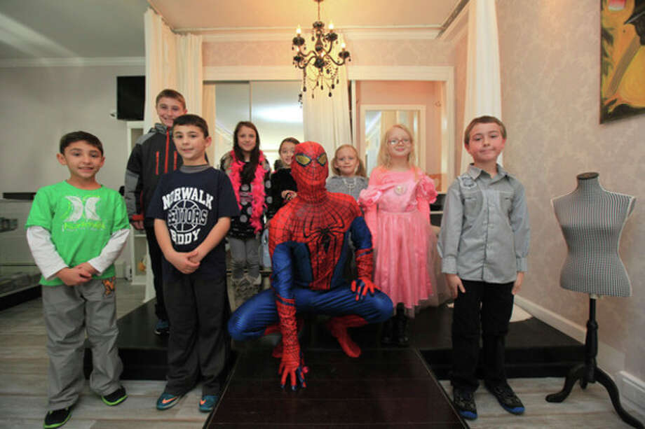 Hour photo / Chris Palermo. Children pose with Spiderman at the grand opening of the Children's Party Place at 21 First St. Saturday. / © 2013 Hour Newspapers All Rights Reserved.