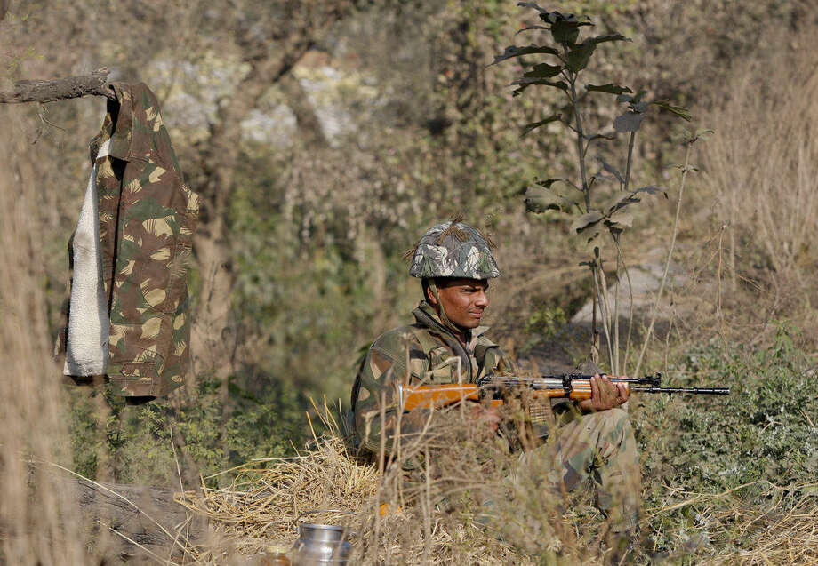 An Indian army soldier takes position outside the Pathankot air force base in Pathankot, India, Sunday, Jan. 3, 2016. Combing operations to secure the Indian air force base where a group of militants started an attack before dawn on Saturday were continuing late Sunday morning. (AP Photo/Channi Anand)