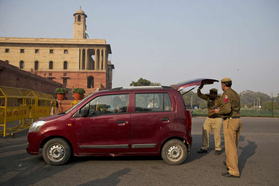 Indian policemen check a car near the Presidential Palace as part of enhanced security measures following the attack on an air force base near the country's border with Pakistan, New Delhi, India, Sunday, Jan. 3, 2016. A top government official says Indian troops are still battling at least two gunmen at the Pathankot air force base more than 36 hours after the compound came under attack. (AP Photo /Tsering Topgyal)