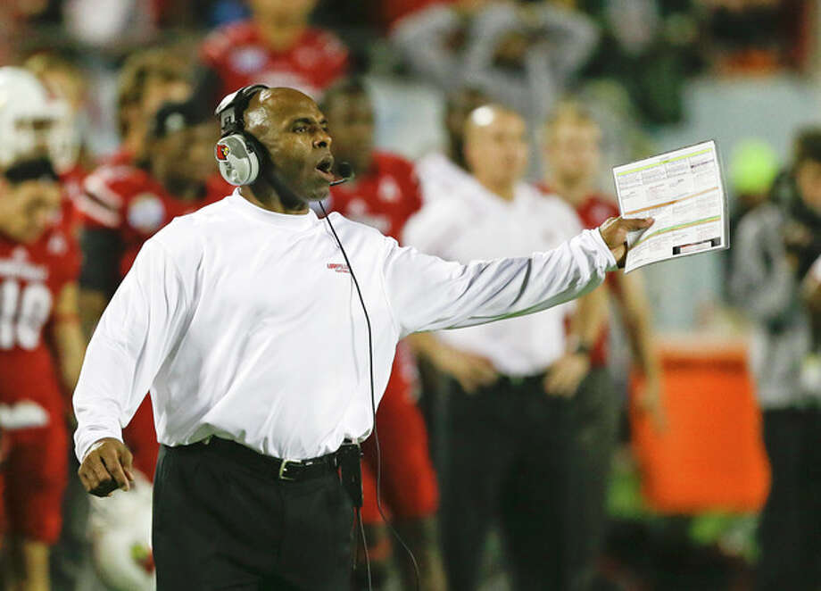 FILE - In this Dec. 28, 2013, file photo, Louisville head coach Charlie Strong calls out to players on the field during the second half of the Russell Athletic Bowl NCAA college football game against Miami in Orlando, Fla. Strong remains Louisville's football coach for the moment, telling assistants Saturday morning, Jan. 4, 2014, he hasn't decided to accept Texas' offer to become its coach. (AP Photo/John Raoux, File) / AP