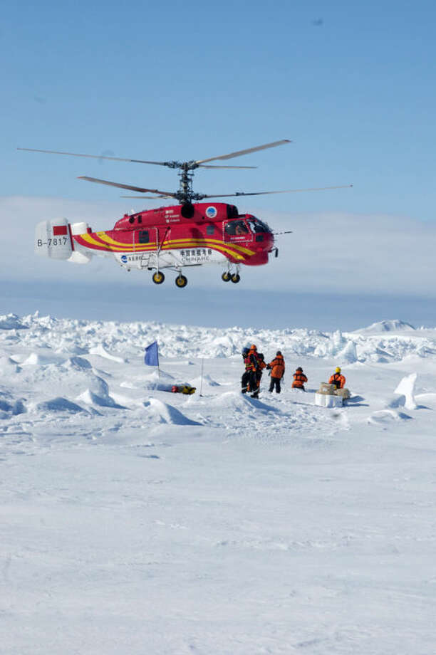 CORRECTS TO AUSTRALASIAN ANTARCTIC DIVISION -In this image provided by Australasian Antarctic Division, passengers trapped for more than a week on the icebound Russian research ship MV Akademik Shokalskiy are rescued by a Chinese helicopter, Thursday, Jan. 2, 2014. The helicopter rescued all 52 passengers from the research ship that has been trapped in Antarctic ice, 1,500 nautical miles south of Hobart, Australia, since Christmas Eve after weather conditions finally cleared enough for the operation Thursday. (AP Photo/Australasian Antarctic Division, Jessica Fitzpatrick) EDITORIAL USE ONLY, ONE TIME USE ONLY, NO ARCHIVES; NO SALES