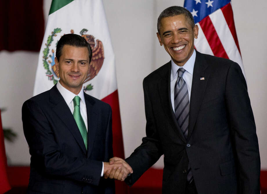 FILE - In this Feb. 19, 2014 file photo, Mexico's President Enrique Pena Nieto, left, and President Barack Obama pose for photographers at the North American Leaders Summit in Toluca, Mexico. Obama is hosting Nieto at the White House Tuesday, Jan. 6, 2015, looking to his southern neighbor for help implementing his changing policies on immigration and Cuba. (AP Photo/Eduardo Verdugo, File)