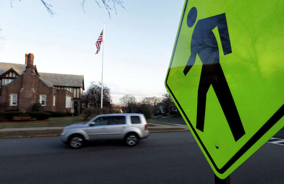 In this Dec. 27, 2013, photo a vehicle drives in front of Forest Avenue Elementary School in Glen Ridge, N.J. A presidential commission appointed by President Barack Obama is grappling with concerns that some schools no longer want to serve as polling places amid security concerns since the shooting in Newtown, Conn. Among those schools that have closed to balloting is Forest Avenue Elementary School. (AP Photo/Julio Cortez) / AP