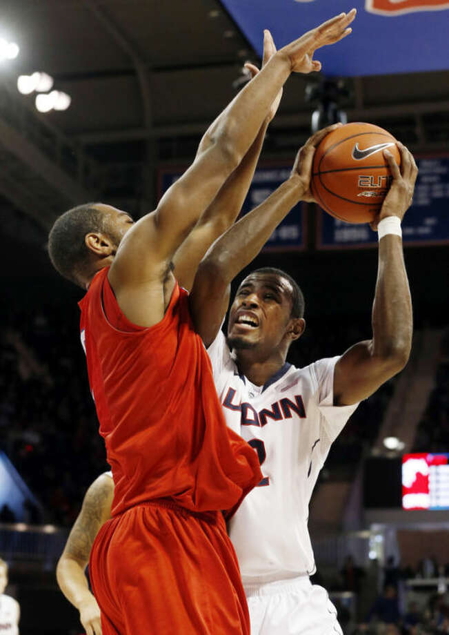 Connecticut forward DeAndre Daniels (2) tries to get a shot over SMU forward Shawn Williams (2) during the first half of a NCAA basketball game on Saturday, Jan. 4, 2014, in Dallas.  (AP Photo/John F. Rhodes)