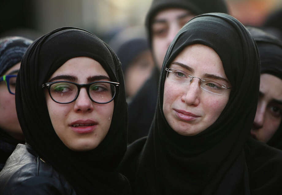 Sisiters of Ali Khadra, who was killed Thursday by a car bomb explosion, weep as they attend their brother's funeral procession in the southern suburb of Beirut, Lebanon, Saturday, Jan. 4, 2014. An explosion tore through a crowded commercial street Thursday in a south Beirut neighborhood that is bastion of support for the Shiite group Hezbollah, killing several people, setting cars ablaze and sending a column of black smoke above the Beirut skyline. (AP Photo/Hussein Malla) / AP