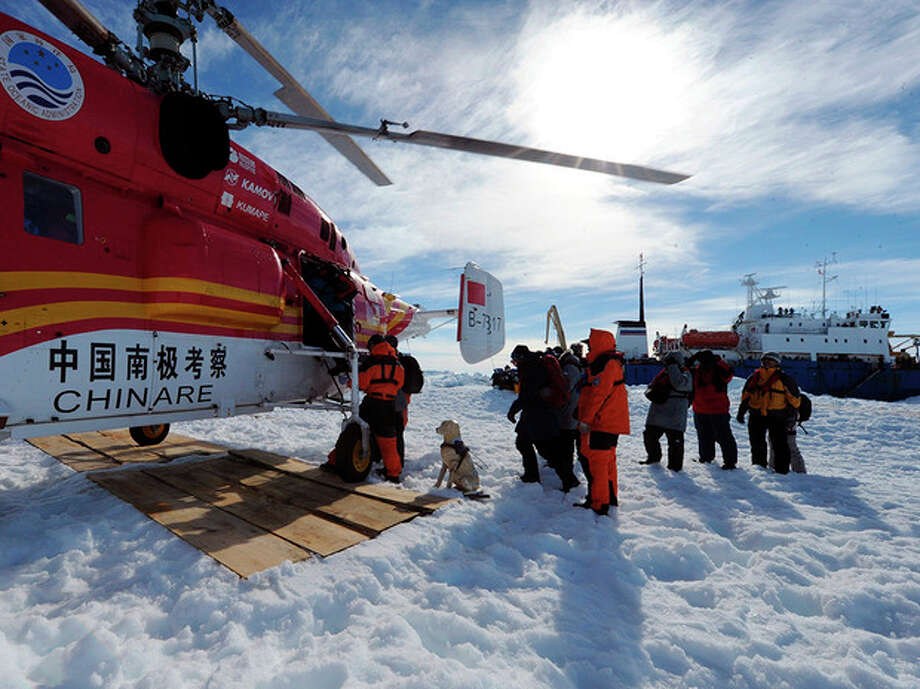 AP Photo / Xinhua, Zhang JiansongPassengers from the trapped Russian vessel MV Akademik Shokalskiy, seen at right, prepare to board the Chinese helicopter Xueying 12 in the Antarctic Thursday. / Xinhua