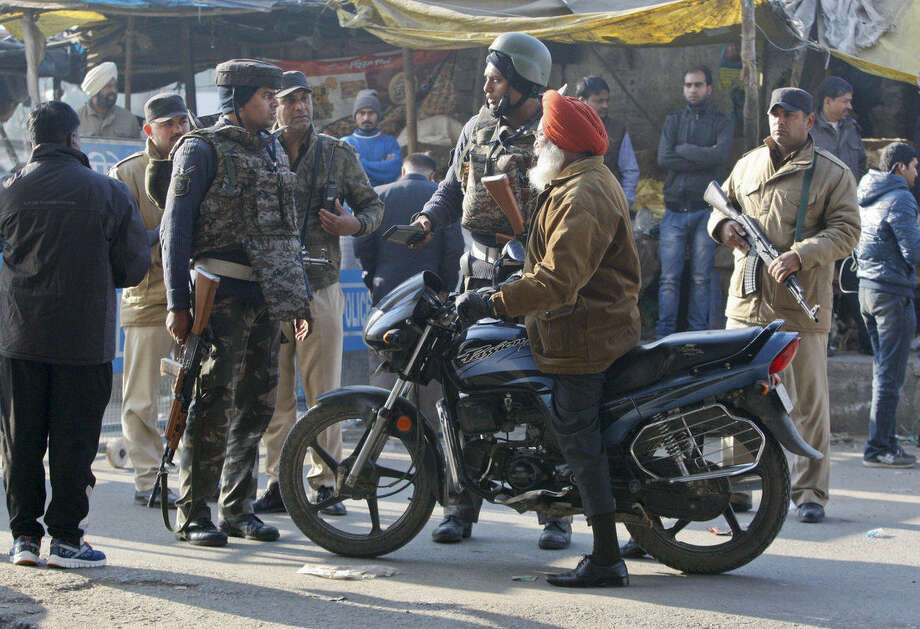 Indian security men stop a commuter outside the Pathankot air force base in Pathankot, India, Sunday, Jan. 3, 2016. Combing operations to secure the Indian air force base where a group of militants started an attack before dawn on Saturday were continuing late Sunday morning. (AP Photo/Channi Anand)