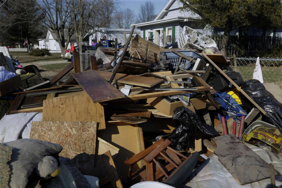 Residents pile ruined furniture, appliances and clothes along the street for disposal crews to pick up after last week's flooding from the south fork of the Sangamon River, Sunday, Jan. 3, 2016, in Kincaid, Ill. Gov. Bruce Rauner toured flood-damaged homes Sunday in the 1,400-resident central Illinois town. (AP Photo/Seth Perlman)