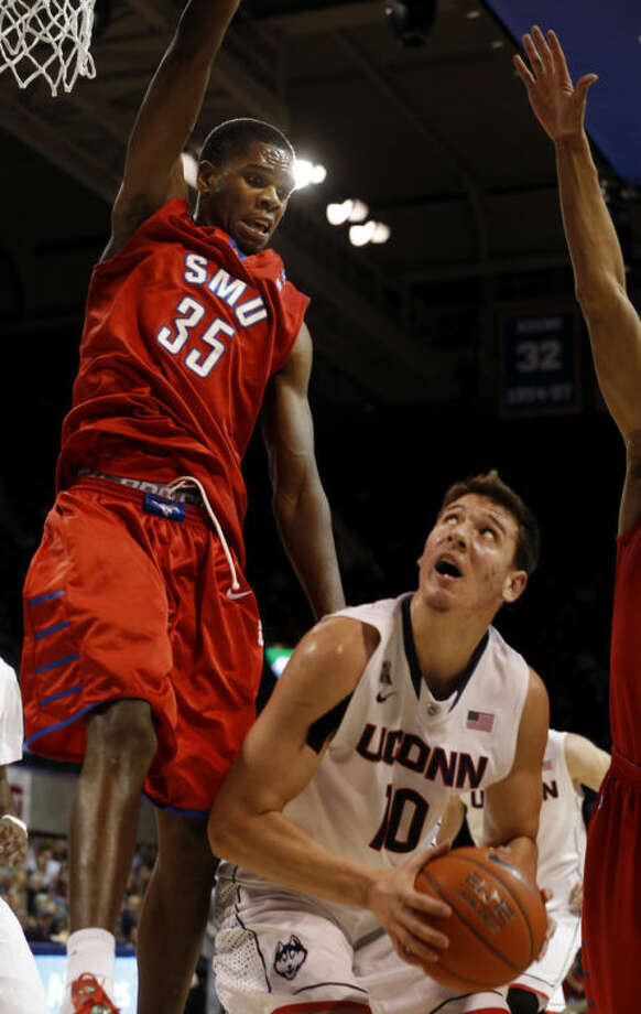 SMU center Yanick Moreira (35) leaps high to try to defend a shot by Connecticut forward Tyler Olander (10) during the first half of a NCAA basketball game on Saturday, Jan. 4, 2014, in Dallas.  (AP Photo/John F. Rhodes)