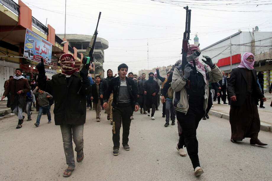 Mourners and Sunni gunmen chant slogans against Iraq's Shiite-led government during the funeral of a man killed when clashes erupted between al-Qaida gunmen and Iraqi army soldiers on Friday, his family said, in Fallujah, 40 miles (65 kilometers) west of Baghdad, Iraq, Saturday, Jan. 4, 2014. Provincial spokesman Dhari al-Rishawi said Iraqi security forces and allied tribesmen are pressing their campaign to rout al-Qaida from Fallujah and Ramadi, two main cities in the western Anbar province. (AP Photo) / AP